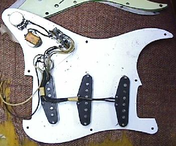 shielding plate around the pots, and the white single layer pickguard   at the top edge is a early 1960's three-layer celluliod